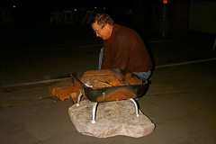 Harry Heflin prepares the campfire -- Click to Enlarge